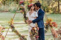 02 a tall triangle wedding altar with fall leaves, lush blooms and candles for a fall wedding