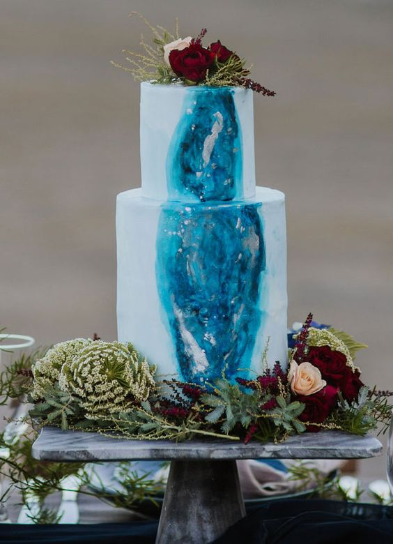 a watercolor blue wedding cake with a bold blue detail and some metallic touches plus bold blooms on top