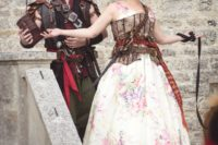 02 the couple wearing customized pirate costumes – a floral dress with a corset and belts and a costume of a pirate with lots of details
