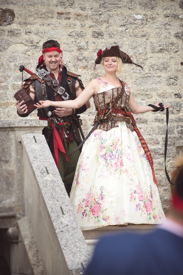 the couple wearing customized pirate costumes   a floral dress with a corset and belts and a costume of a pirate with lots of details