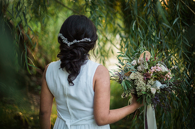 The bride's hairstyle was a curly twisted one with a stunning hair vine as an accent