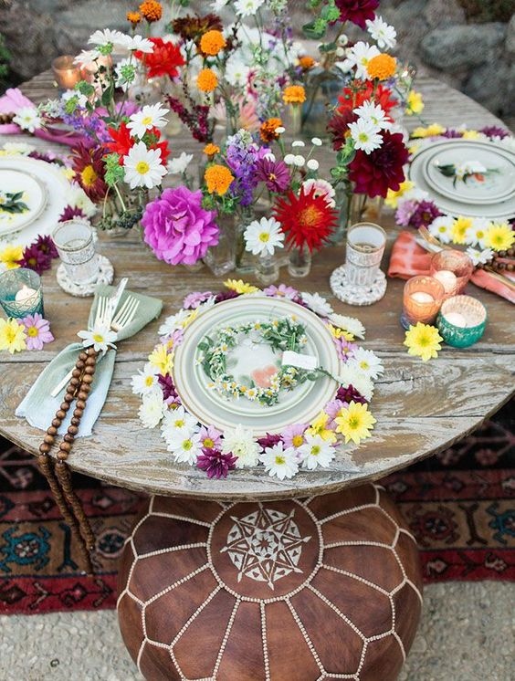 a bold picnic setting with Moroccan poufs as seats, a round table and lots of colorful blooms and details