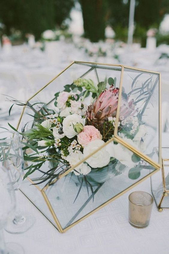 a creative lush floral centerpiece in a diamond-shaped glass terrarium with a gold frame