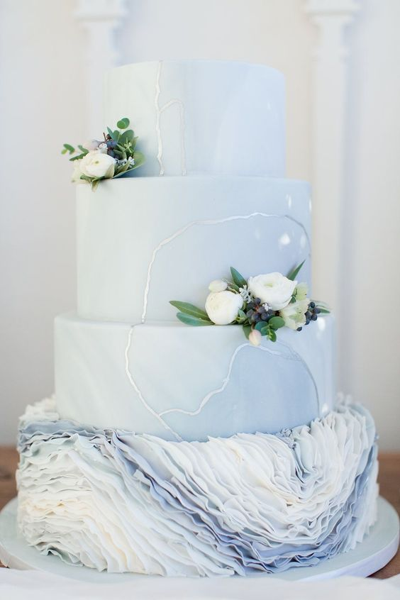 a dusty blue wedding cake with a ruffled white and blue layer and some fresh blooms