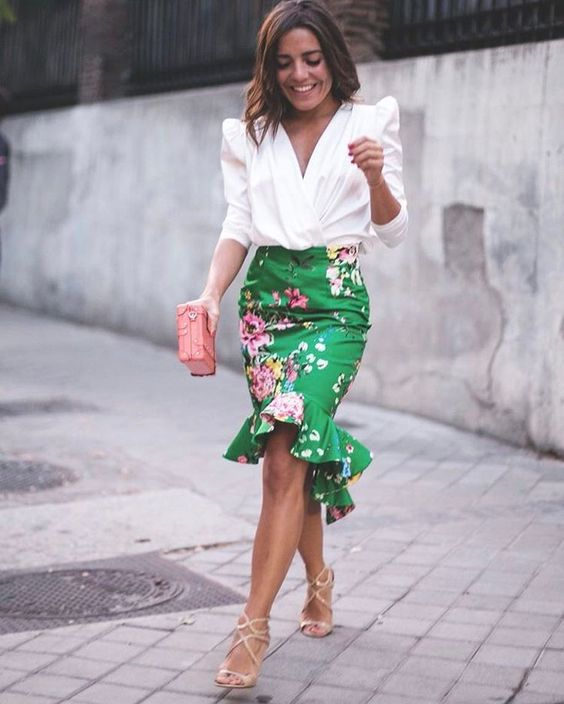 a floral peplum high low green skirt, a white blouse with statement sleeves, strappy heels and a pink clutch