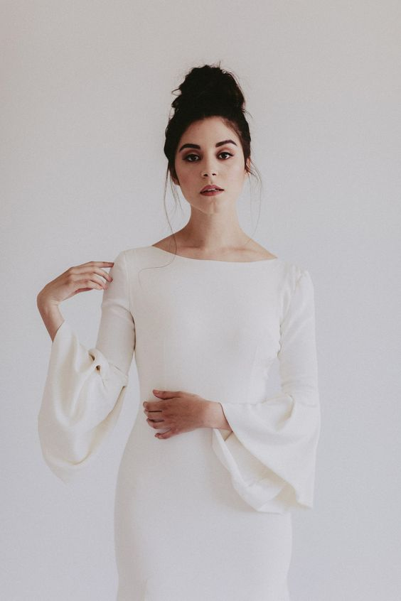 a modern sheath bell sleeve wedding dress with a bateau neckline for a minimalist wedding