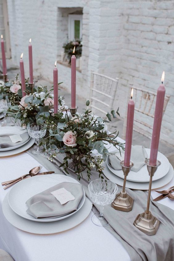 a stylish table setting with dusty pink candles, grey fabrics, eucalyptus and pink rose centerpieces