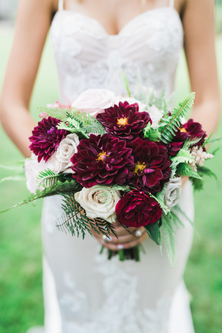 Her bouquet was done with creamy and deep burgundy blooms to highlight the jewel color scheme