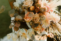 04 She was carrying a lush bouquet with pampas grass, herbs and done in fall-inspired shades of orange and blush