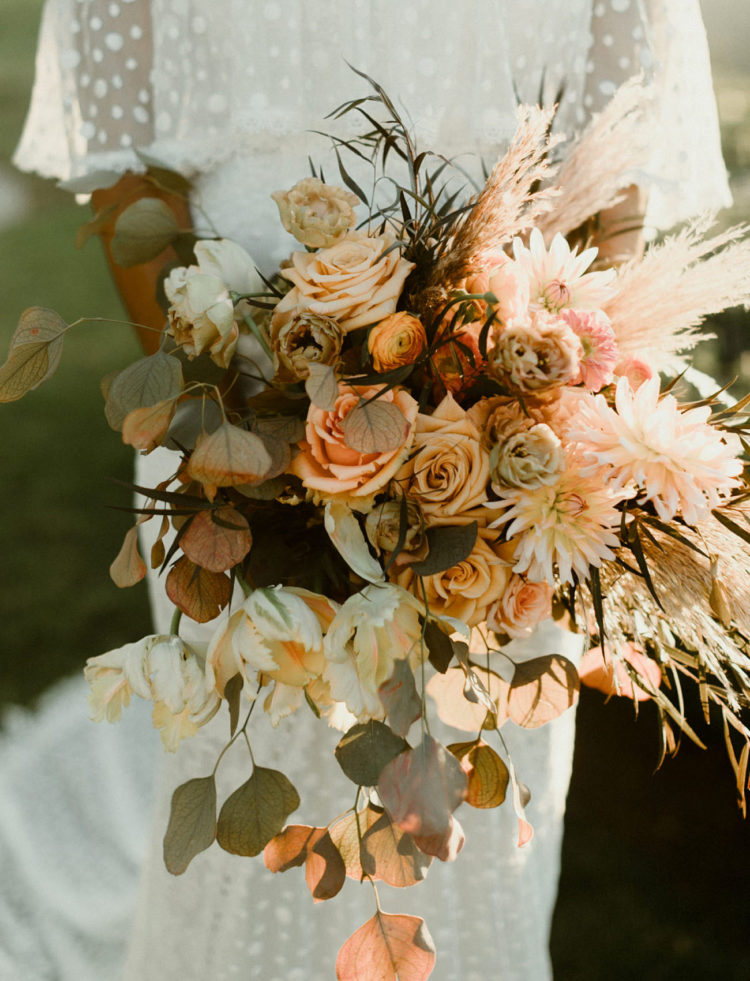 She was carrying a lush bouquet with pampas grass, herbs and done in fall-inspired shades of orange and blush