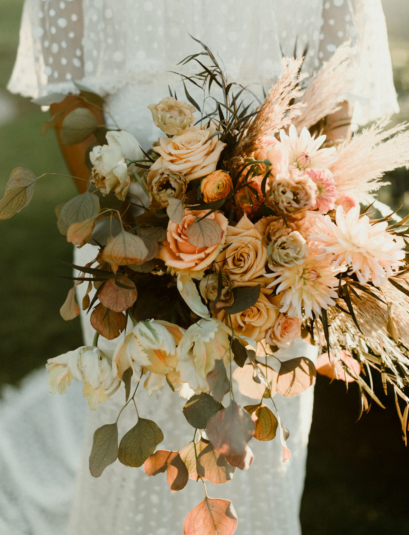 She was carrying a lush bouquet with pampas grass, herbs and done in fall inspired shades of orange and blush