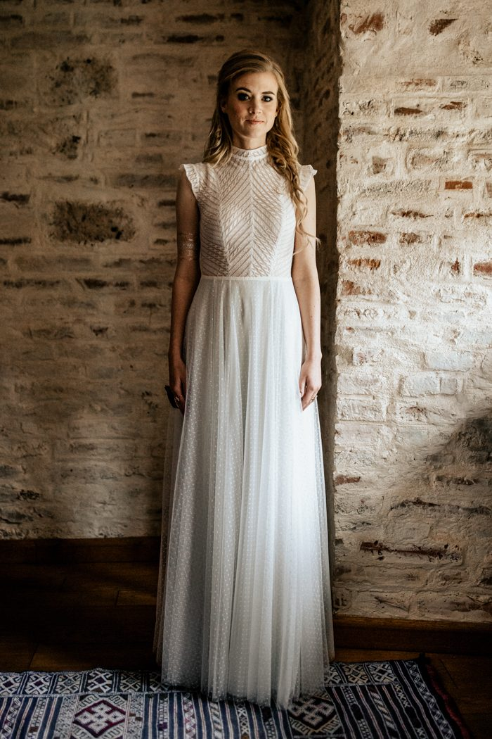 The bride was wearing a whimsy gown with a high neckline and cap sleeves