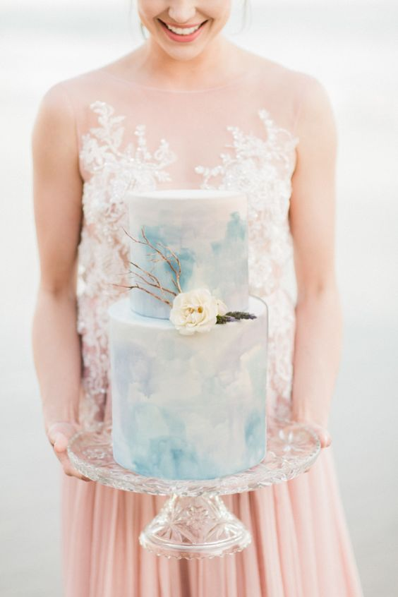 a blue watercolor wedding cake with a white bloom and some branches