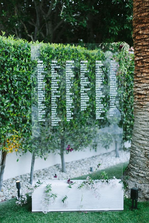 a large acrylic seating chart on a white wooden block with fresh greenery and flowers