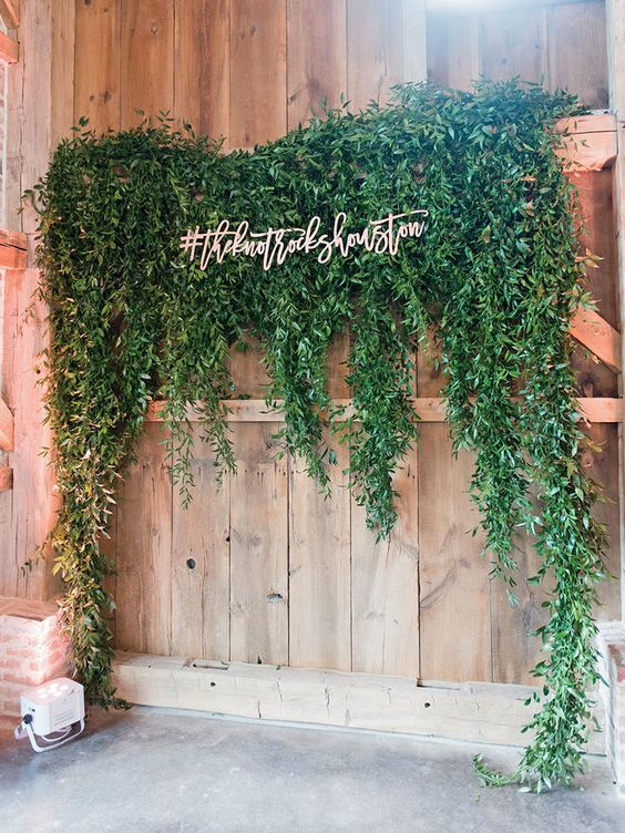 a modern wedidng backdrop or photo booth backdrop of a wooden wall plus greenery