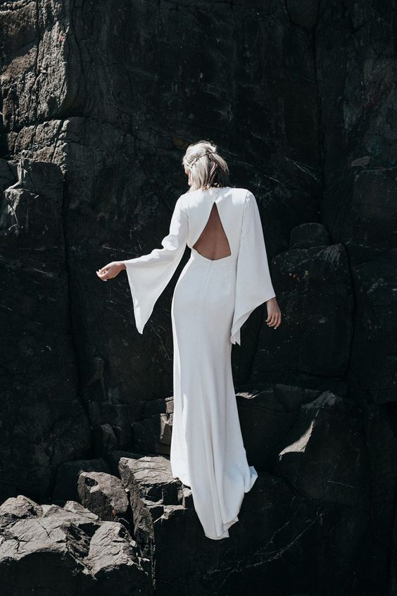 an ultra-modern wedding dress with bell sleeves, a triangle cutout on the back and a high neckline