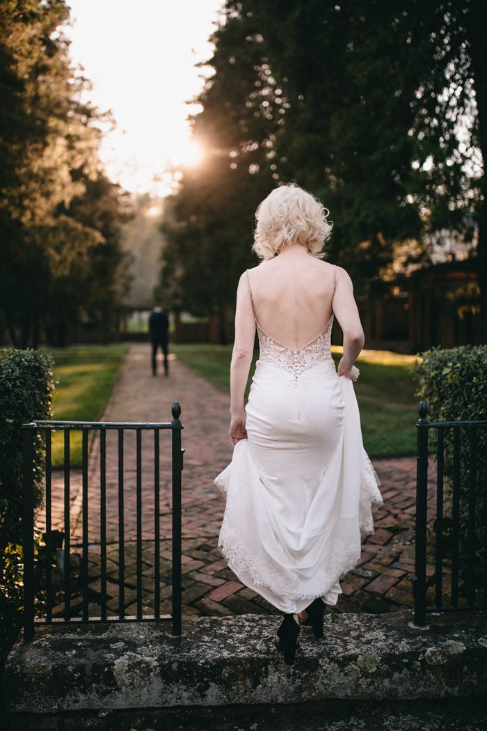 The bride was wearing a jaw dropping wedding dress with spaghetti straps, a lace applique bodice with an open back and buttons on the back