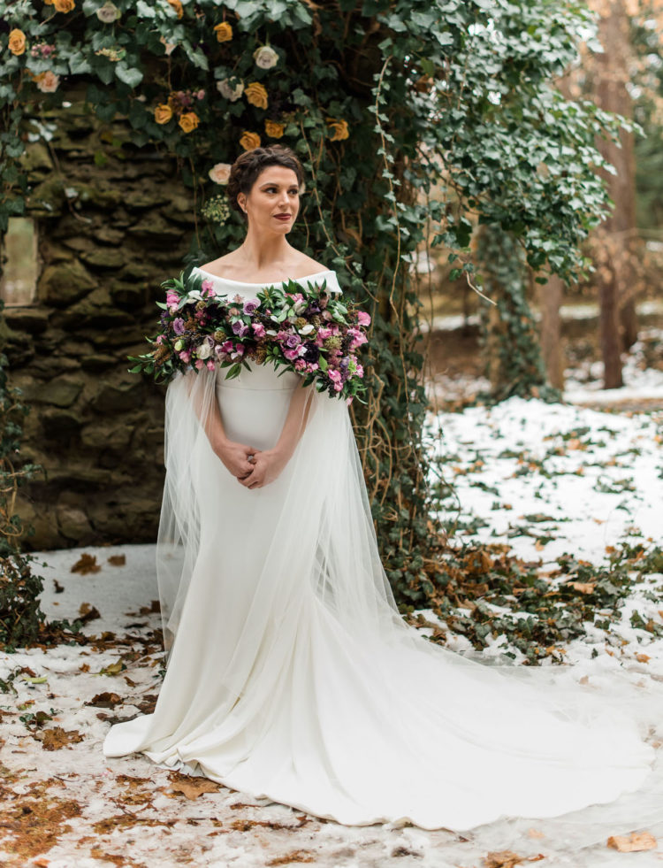 The bride was wearing an amazing off the shoulder gown, a braided updo and a killing fresh flower and greenery cape with tulle