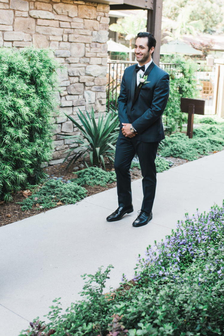 The groom was wearign a navy suit with black lapels and a bow tie
