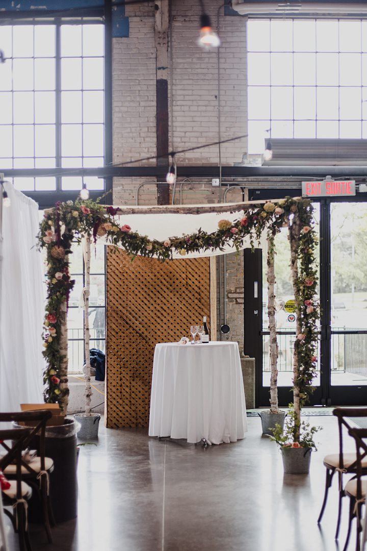 The wedding arch was done with lush florals and birch branches