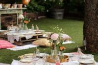 05 a backyard style picnic can be done with pallt tables, vintage pillows and cute florals