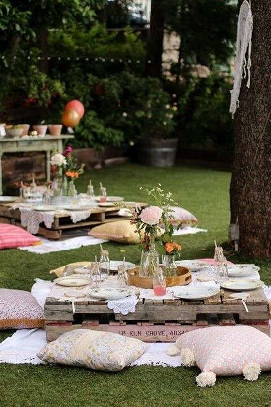 a backyard style picnic can be done with pallt tables, vintage pillows and cute florals