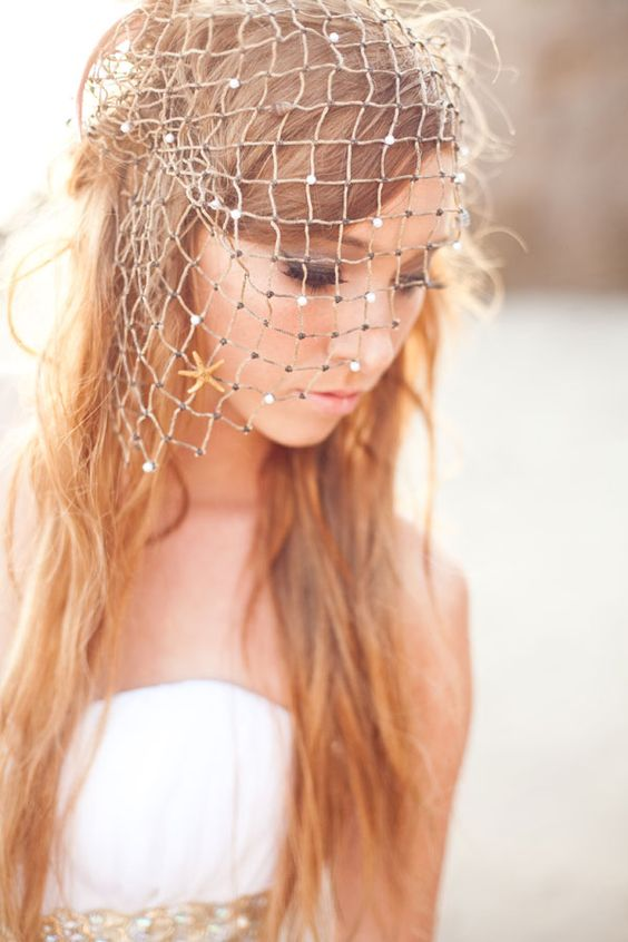 a bride wearing a fishing net with rhinestones, which is a gorgeous accessory