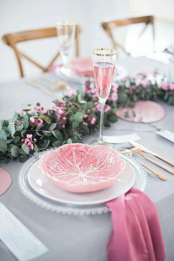 a chic tablescape with a grey tablecloth, a eucalyptus and pink bloom table runner, pink napkins and plates