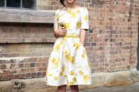 05 a floral A-line knee dress with a thin yellow belt and black heels for a refined look