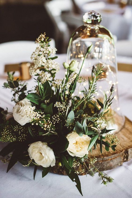 a gorgeous spring centerpiece with neutral blooms, greenery and a cloche with LEDs