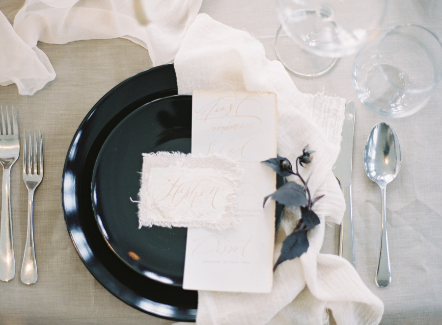 The place setting was done with black plates, exquisite stationery and airy fabrics