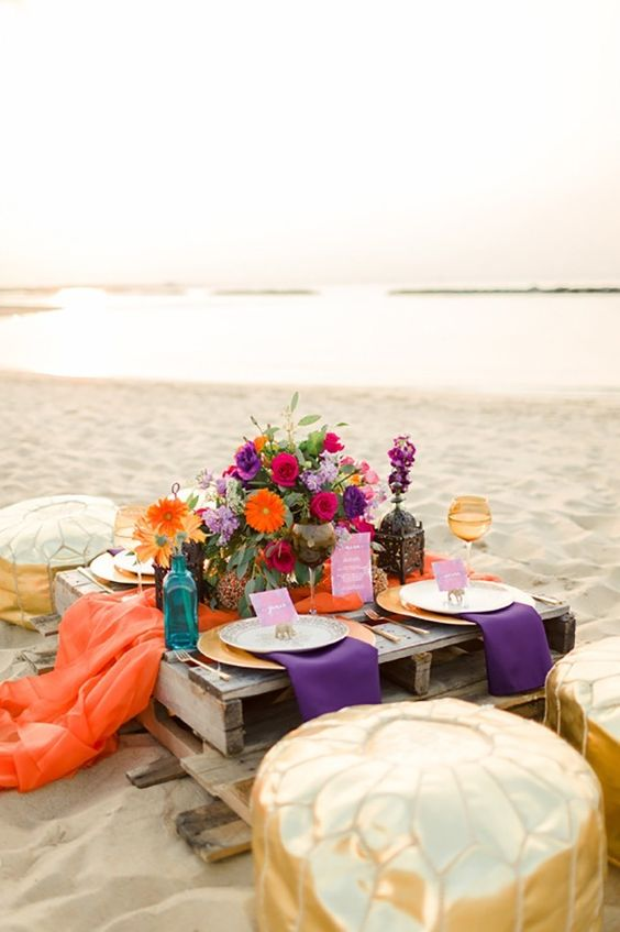 a colorful boho picnic setting with bold florals, linens and gold Moroccan ottomans