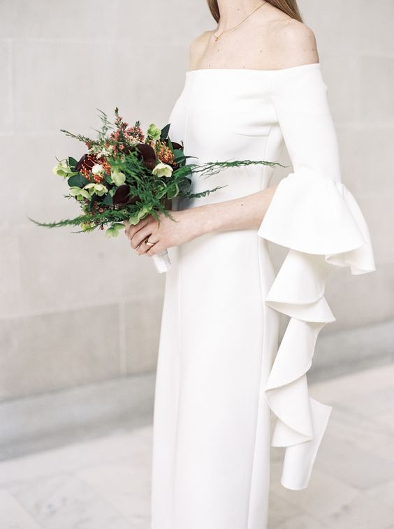 a modern off the shoulder sheath wedding dress with layered ruffled bell sleeves