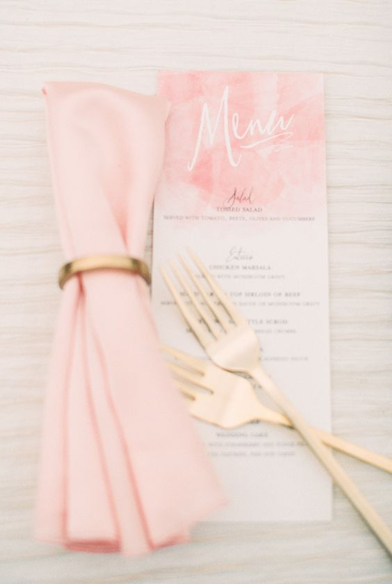 a pink watercolor menu with gold flatware plus a pink napkin and a gold napkin ring