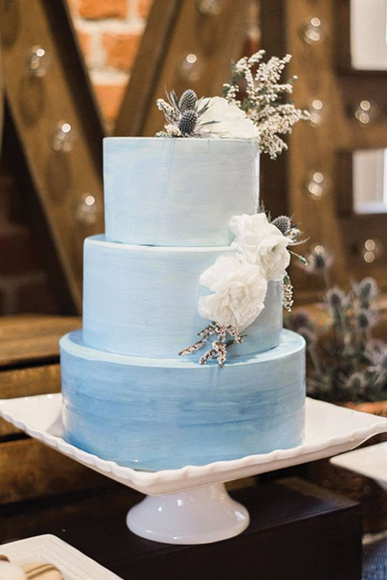 an ombre light blue watercolor wedding cake with white blooms and thistles