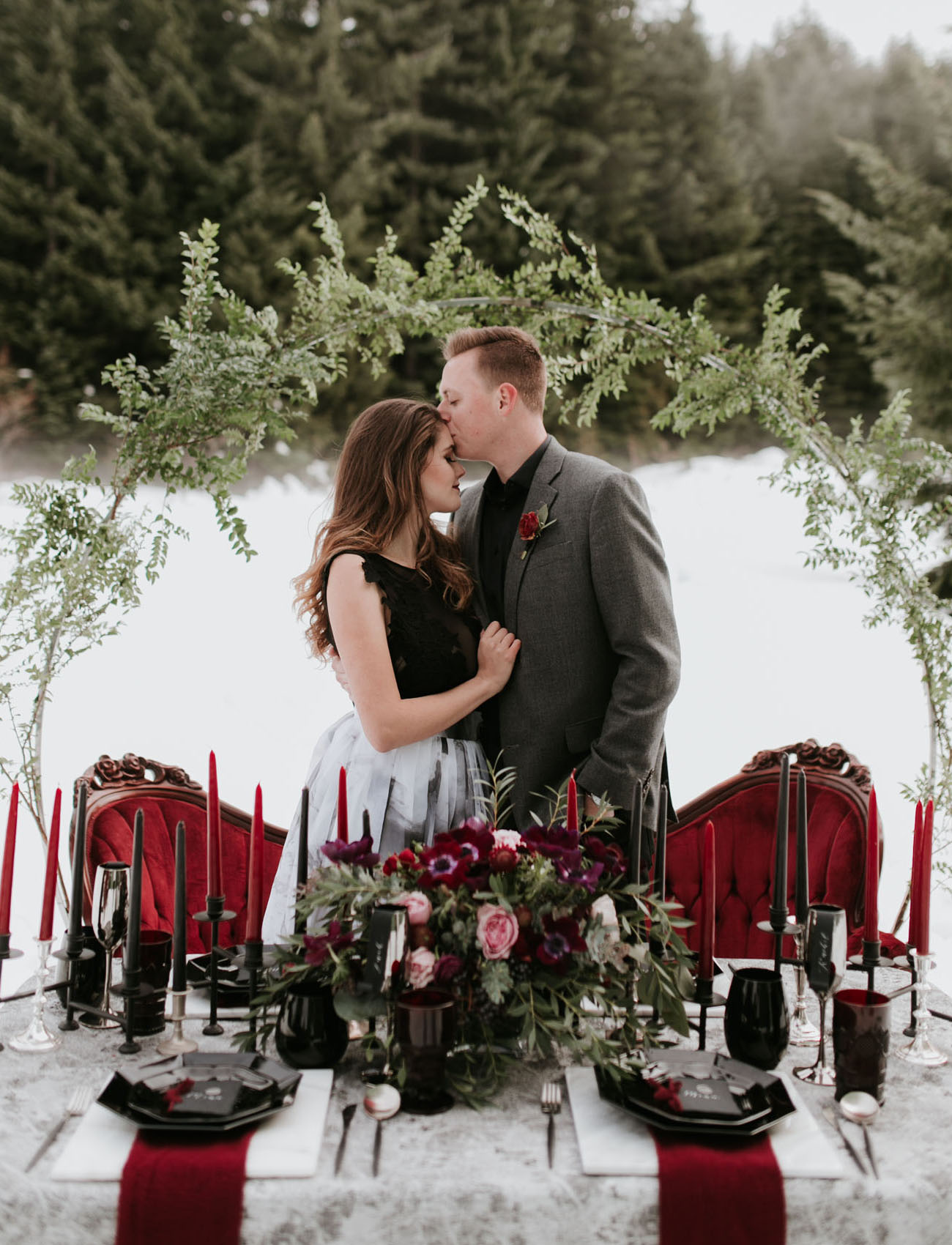 Black glasses, black and red candles, lush florals, black plates and touches of geometry made the wedding decor luxurious