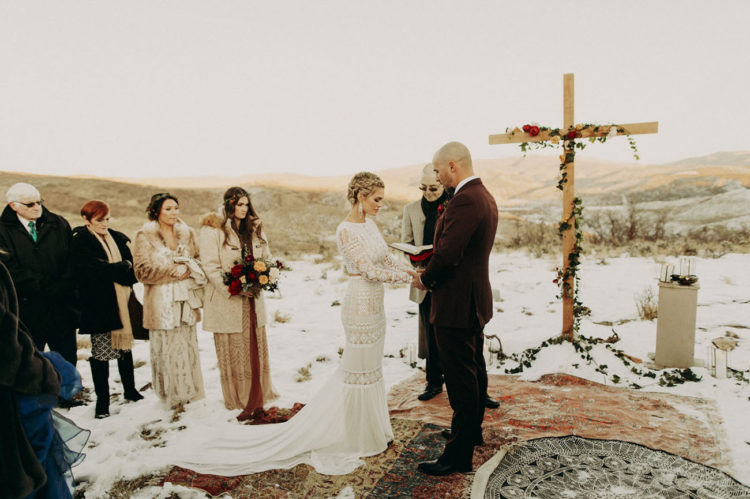 The ceremony space was covered with boho rugs, there was a large cross with greenery and blooms