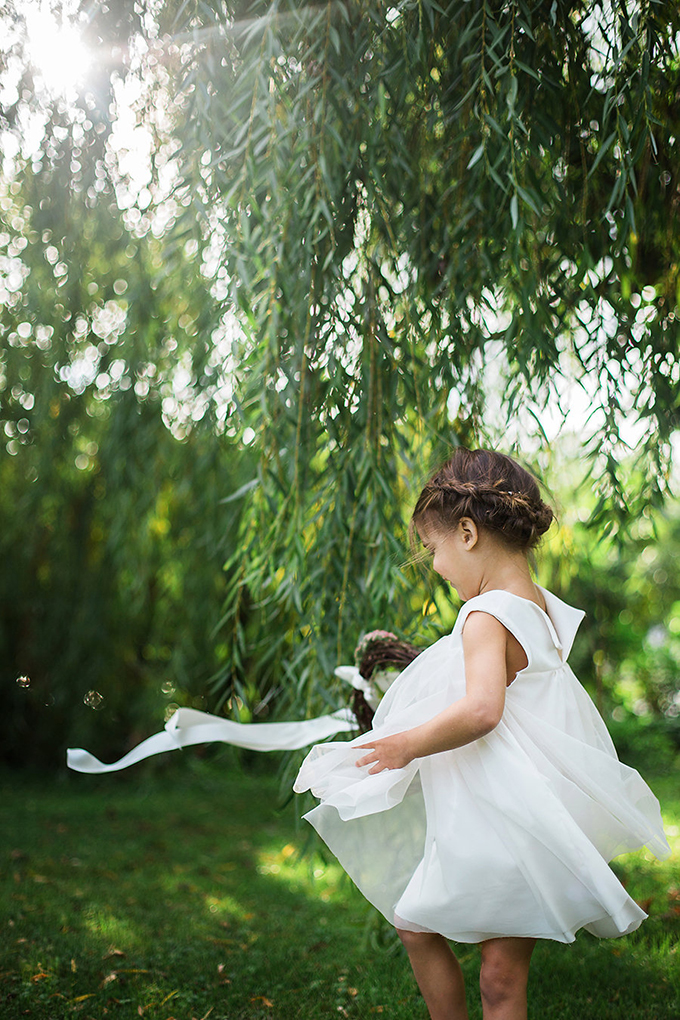 The little flower girl was wearing an airy A line creamy dress and orcking a braided updo