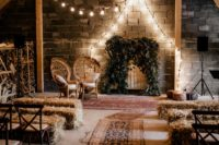 07 The wedding ceremony space was done with hay, boho rugs, boho woven chairs and a lush greenery and feather backdrop