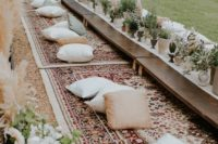 07 a boho-styled picnic with carpets, pillows and low tables and a runner made of herbs and greenery in pots