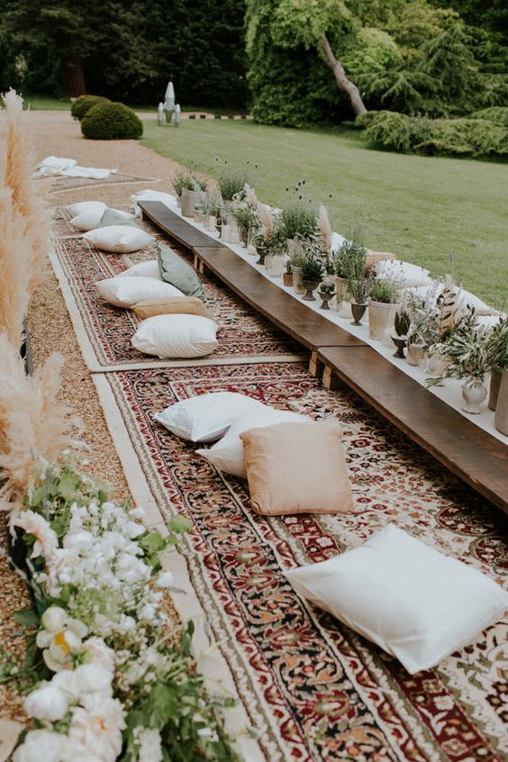 a boho-styled picnic with carpets, pillows and low tables and a runner made of herbs and greenery in pots