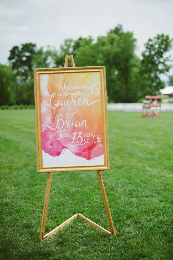 a bright watercolor orange and pink wedding sign in a frame for a summer wedding