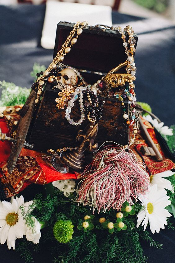 a gorgeous centerpiece of a chest with treasures and a skull plced on greenery and blooms