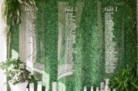 07 a living wall with acrylic seating charts attached and some candles under it
