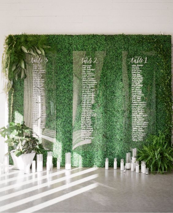 a living wall with acrylic seating charts attached and some candles under it