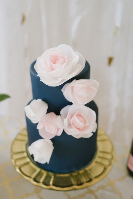 a navy wedding cake topped with pink flowers is an ideal match for this color scheme