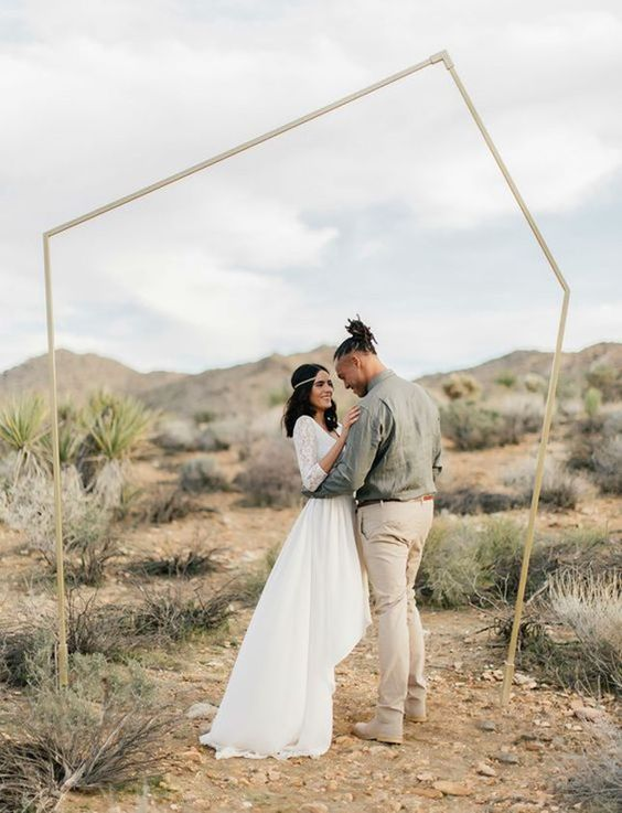 a simple metallic geometric wedding backdrop for an outdoor ceremony