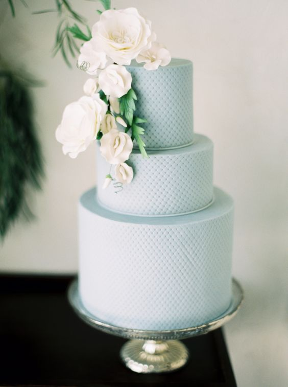 a textural powder blue wedding cake with sugar flowers and greenery for a stylish spring wedding
