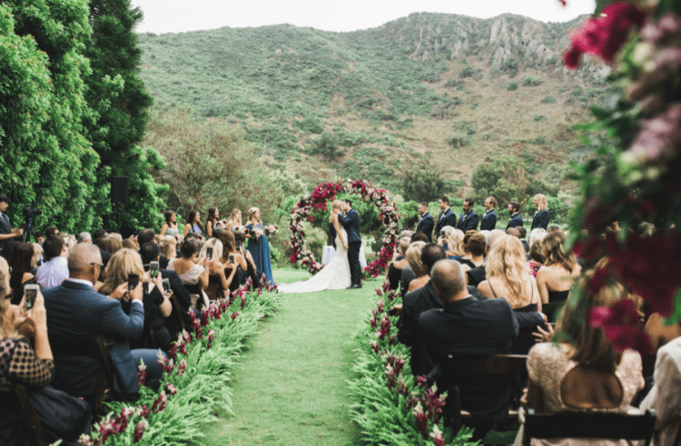 The aisle was also decorated with greenery and jewel tone blooms
