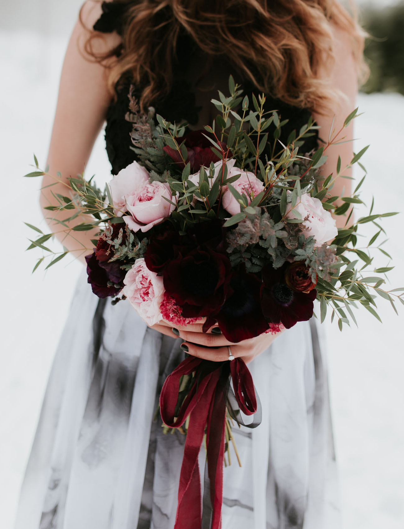 The bride was carrrying a matching bouquet with burgundy velvet ribbon